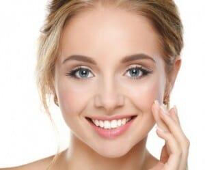 vrouw smeert verzorgingsproduct op gezicht
